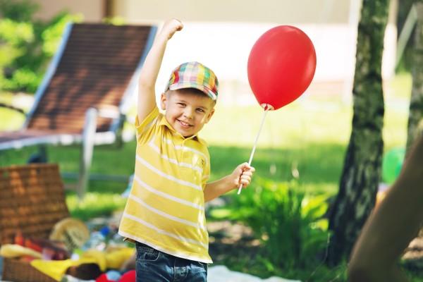 Copil cu balon rosu