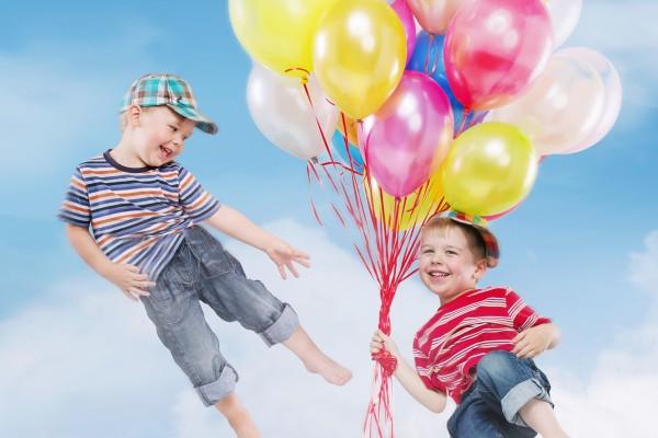 Copii zambitori zburand cu baloane colorate